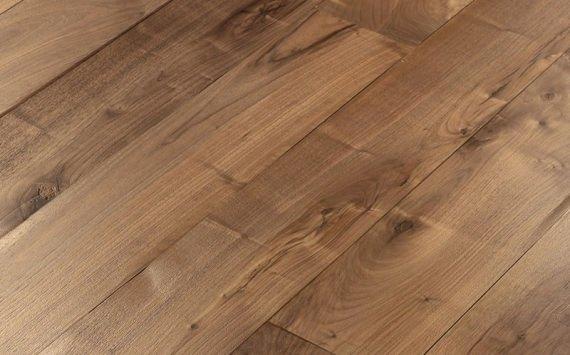Engineered wood planks floor in European Walnut: brushed, aged effect, hand carved, varnished.
