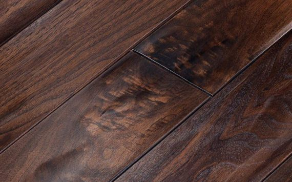 Engineered wood planks floor in American Walnut: aged effect, hand carved, stained, varnished, rounded bevels.