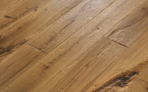 Engineered wood planks floor in Oak: brushed, stained, aged effect, hand carved, varnished.